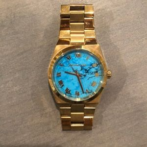 Women's Michael Kors watch with gold band and turquoise face. Needs new battery